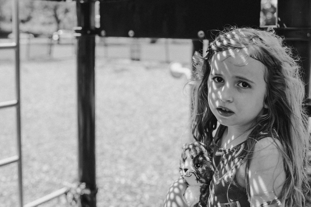 A little girl rests in the shade at Gerry Park.