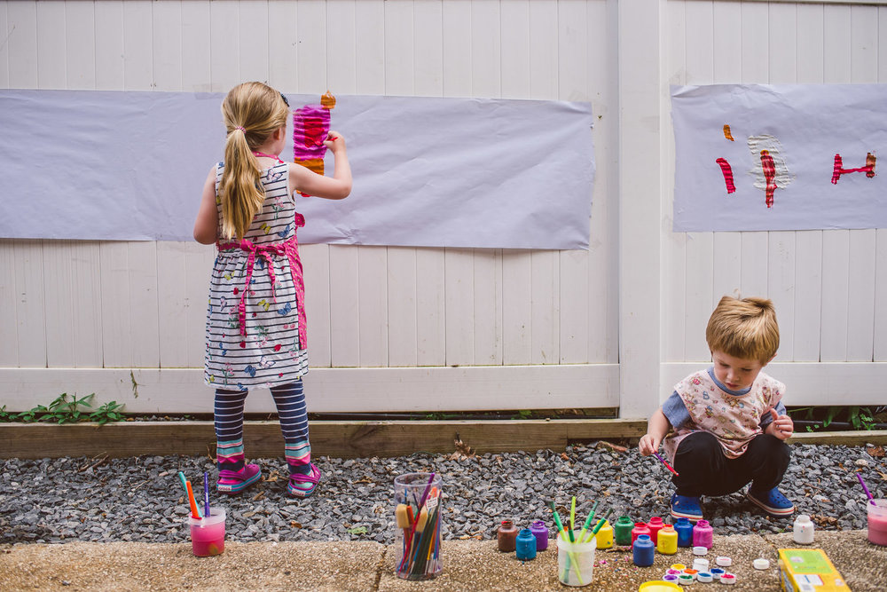 Kids paint outside on butcher paper attached to a fence.