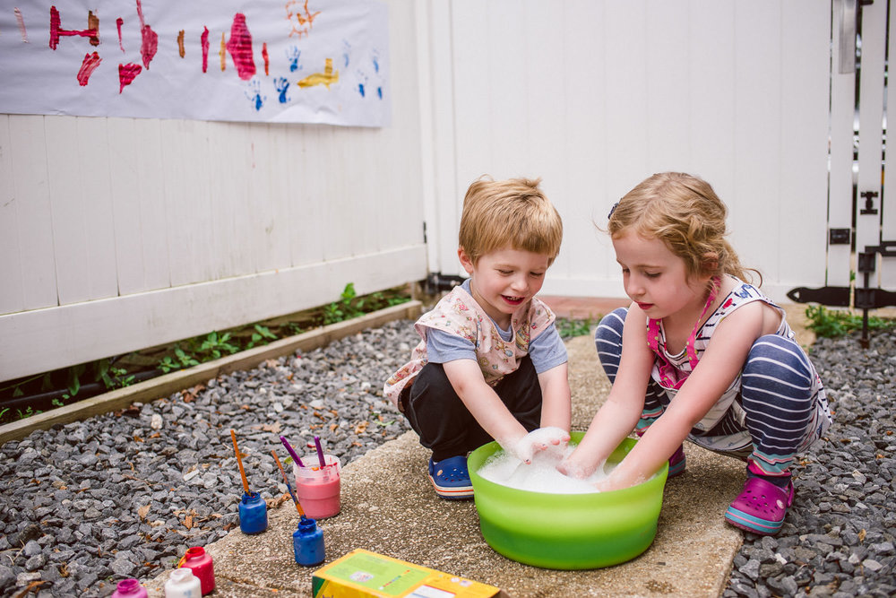 Kids wash their hands in a bowl of soapy water outside.