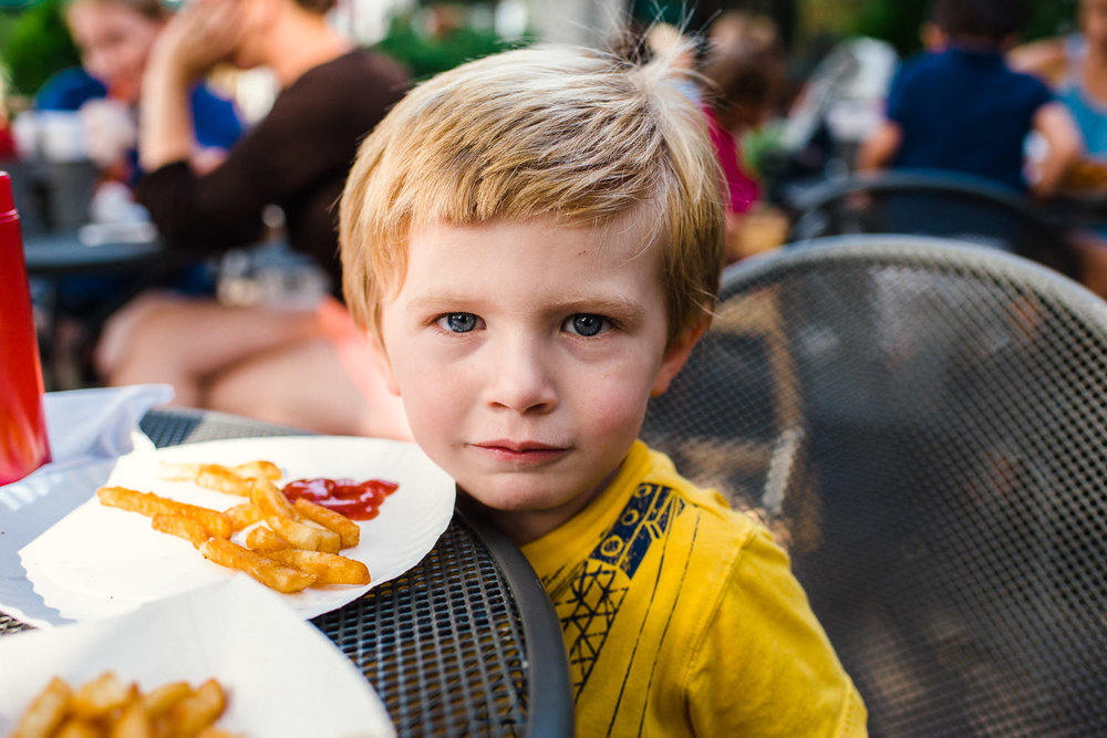 A little boy sits outside and eats fries and ketchup.