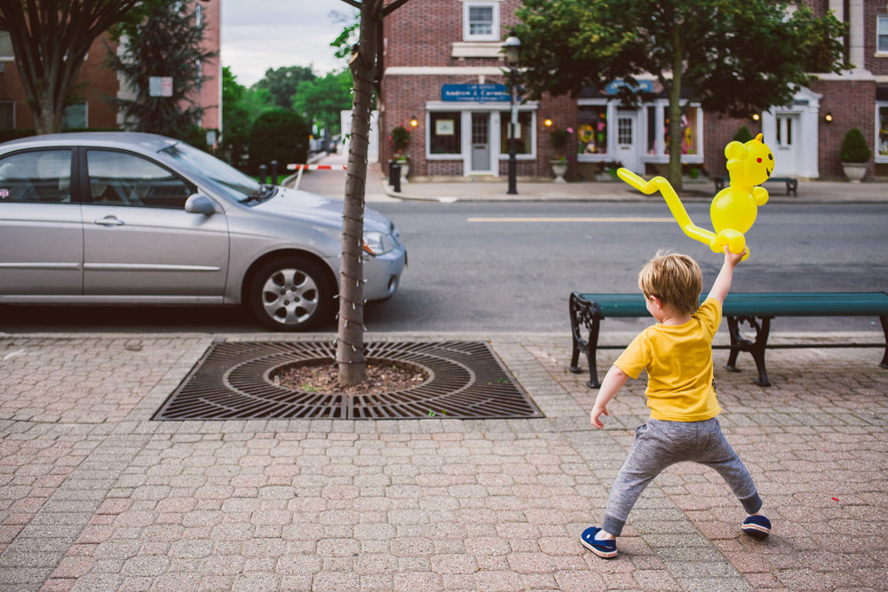 A little boy dances with his Pikachu balloon.