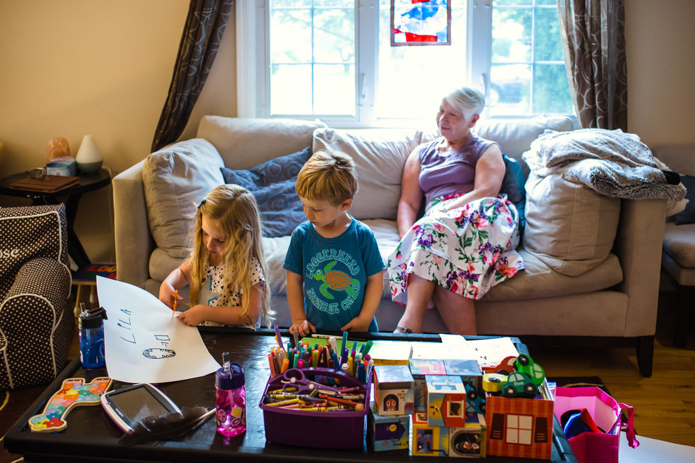 Kids play in the living room while grandmother looks on from the couch.