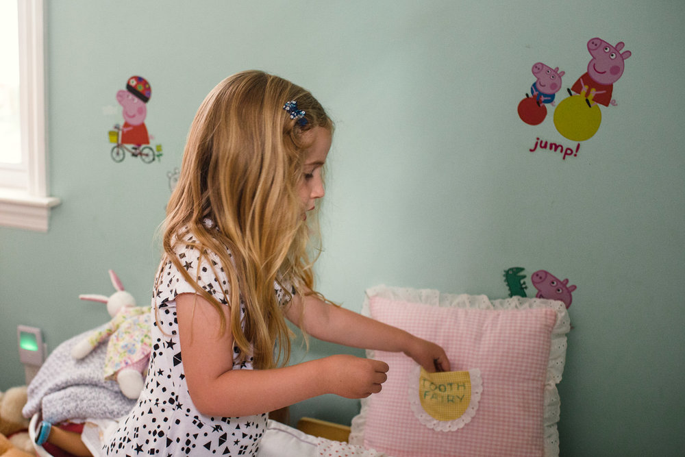 A little girl tucks her tooth into her tooth fairy pillow.