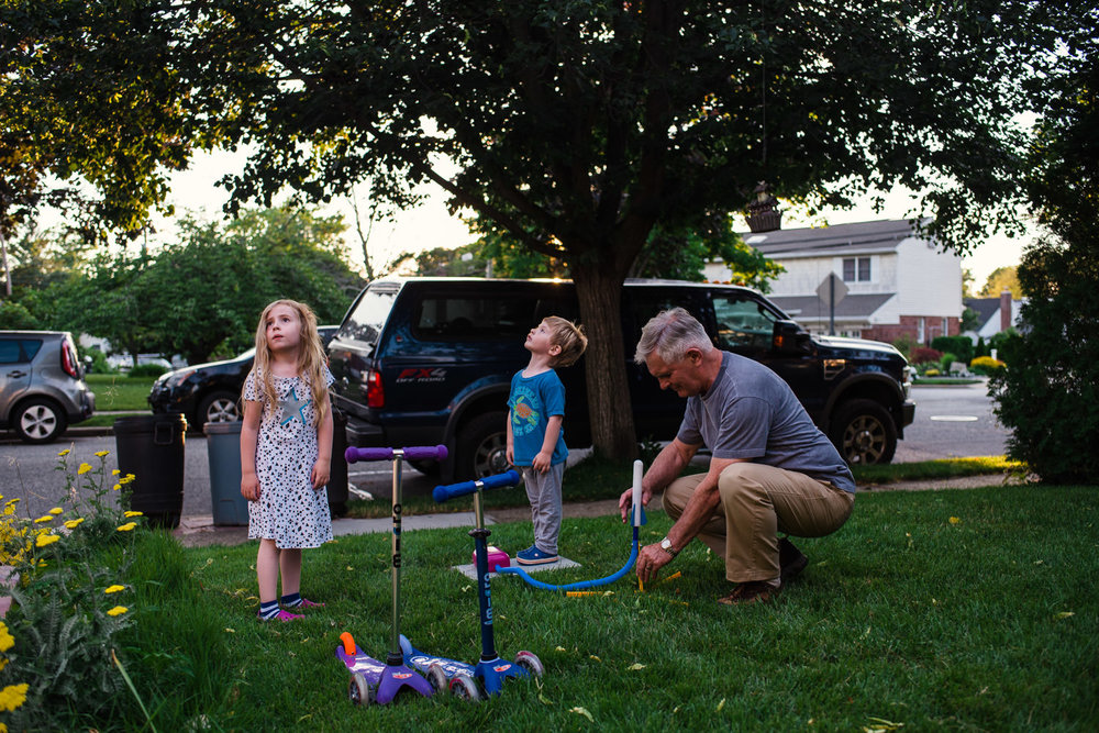 Grandfather plays Stomp Rockets with grandkids.