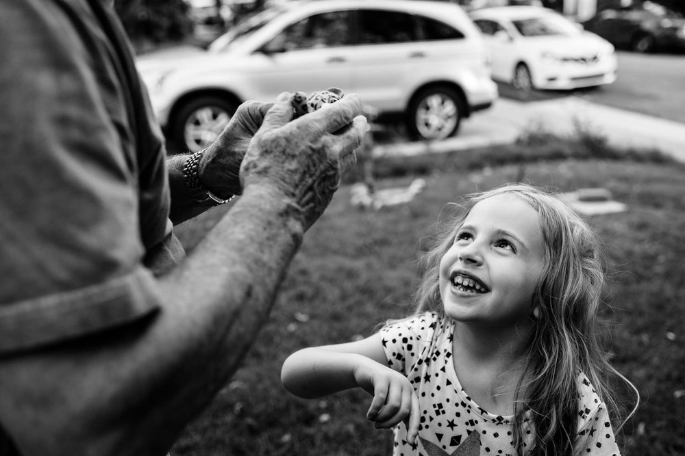 A little girl laughs at her grandfather.