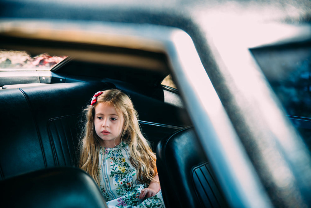 A little girl sits in the backseat of her grandfather's Camaro.
