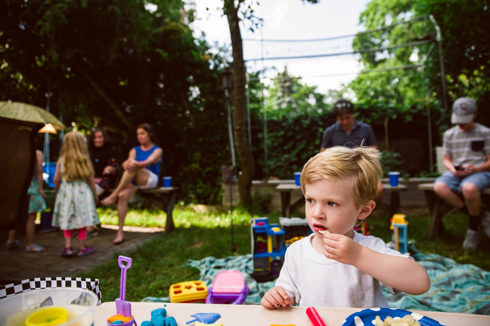 A little boy eats at a backyard barbecue.