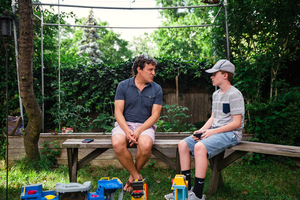 Father and son chat at a backyard barbecue.