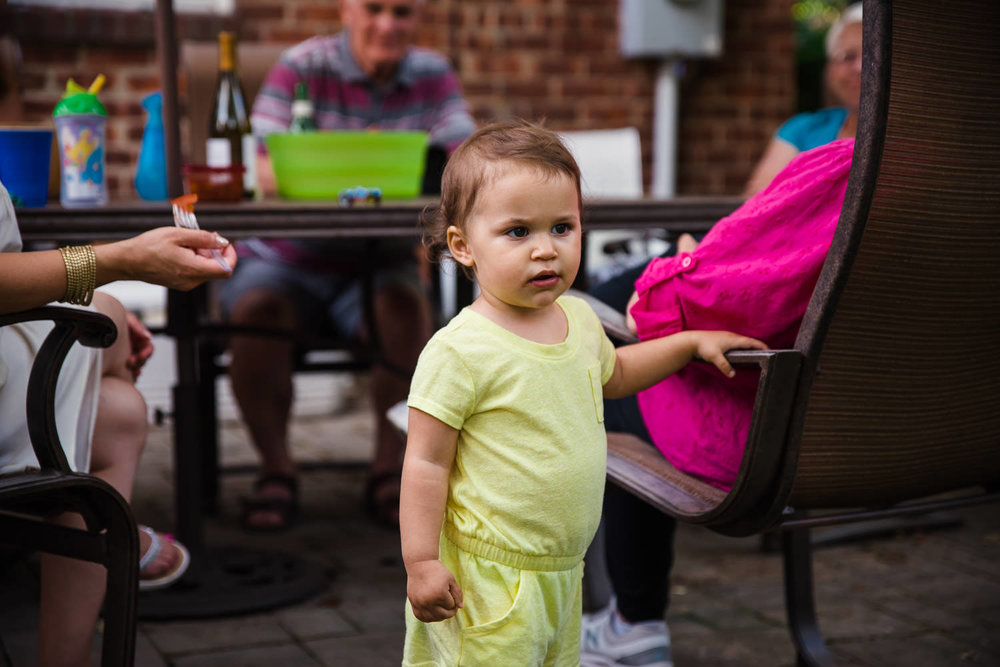 A baby surveys the scene at a backyard barbecue.