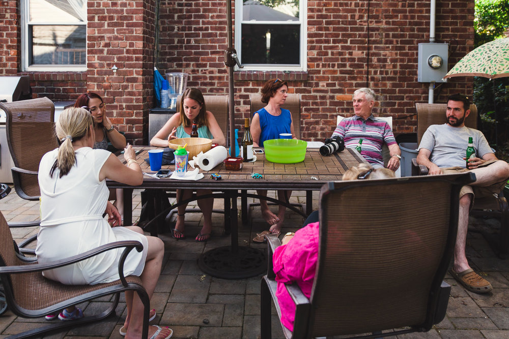 Family members chat at a backyard barbecue party.