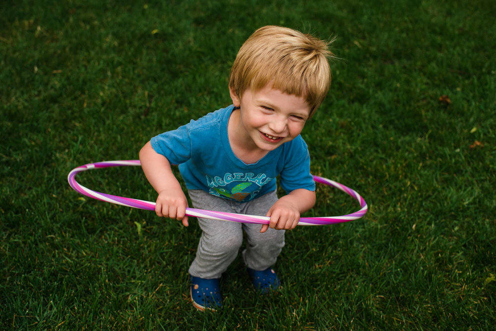 A toddler boy attempts to hula hoop.