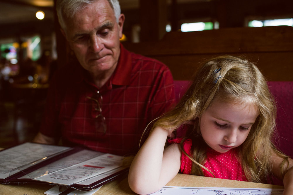 A grandfather and granddaughter look at the menus in a restaurant.