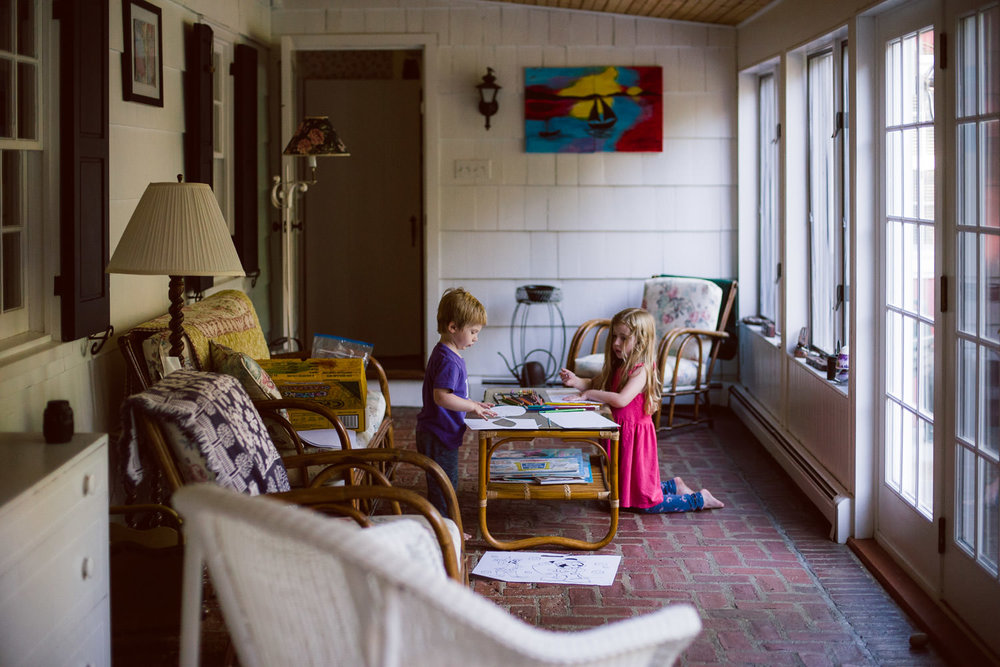 Two kids color in an enclosed porch.