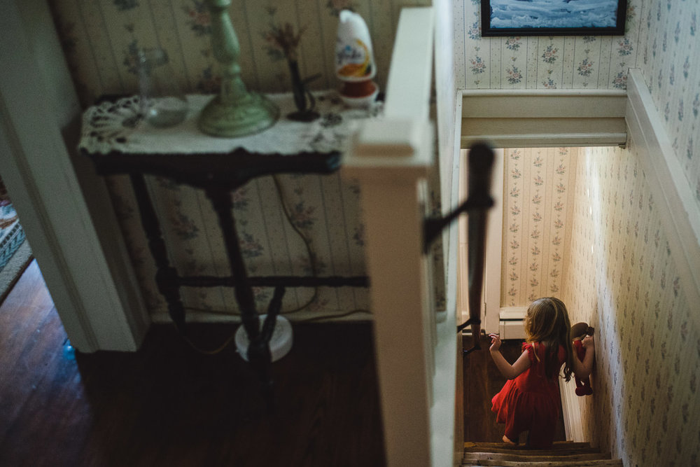 A little girl descends the stairs in an old house.