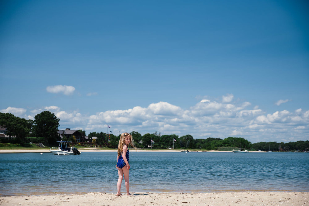 A little girl stands on the shore of the Peconic Bay.