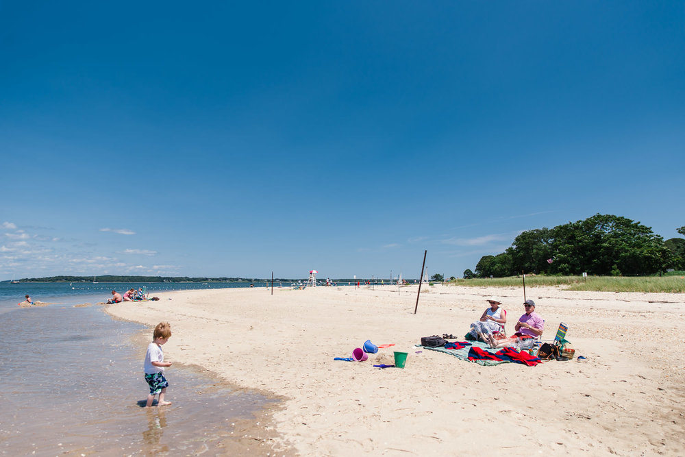 A little boy and his grandparents enjoy the beach at Peconic Bay.