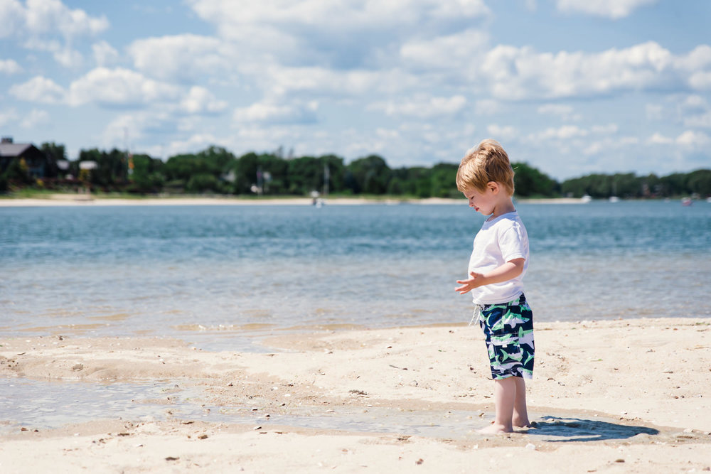A little boy stands on the beach at Peconic Bay.