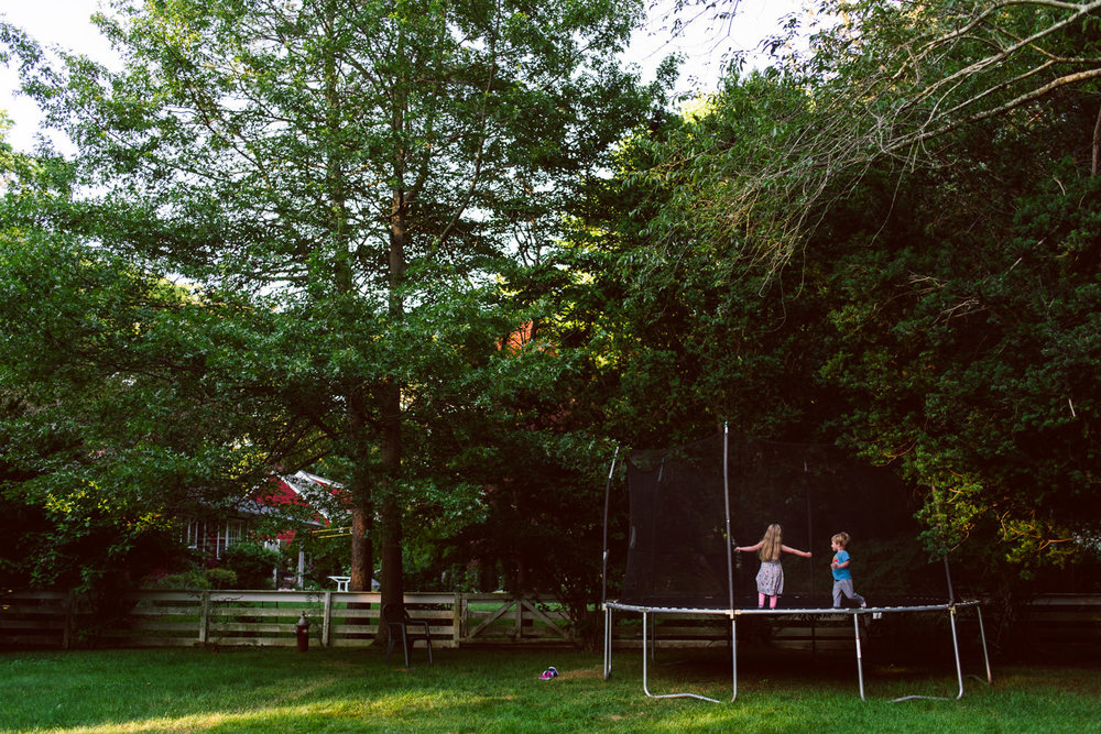 Kids play on a trampoline in the backyard of a house.