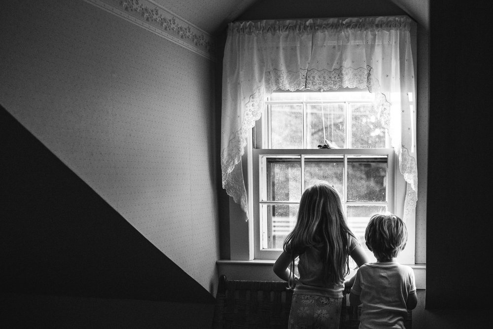 A brother and sister look out a window in an attic room.