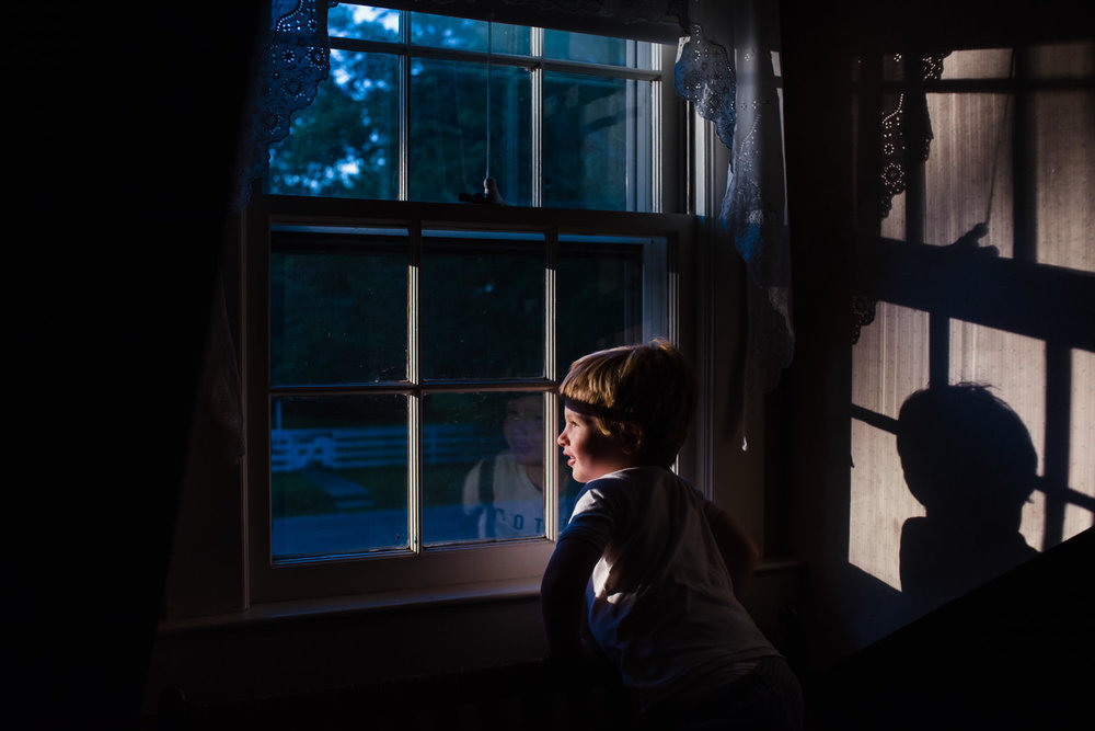 A little boy looks out of a window at sunset.