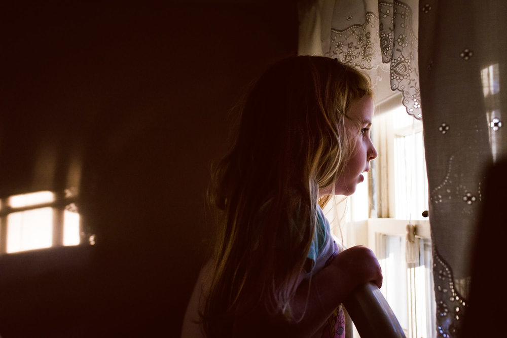 A little girl looks out a bedroom window.