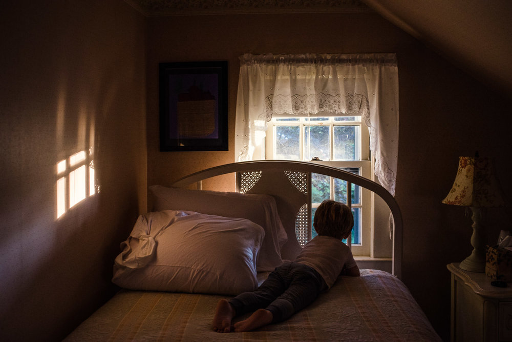 A little boy lies on a bed and looks out the window.