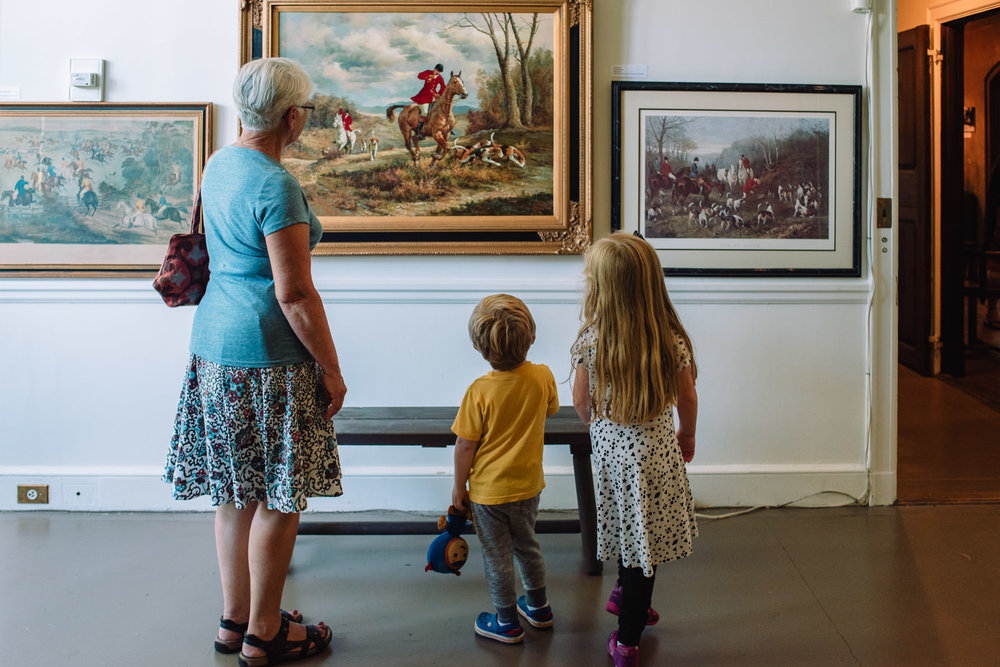A family looks at paintings in the Coe House at Planting Fields.