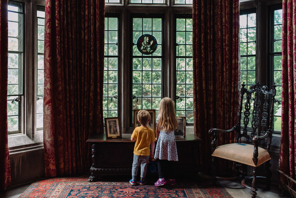 Children look out a window at the Coe House at Planting Fields.