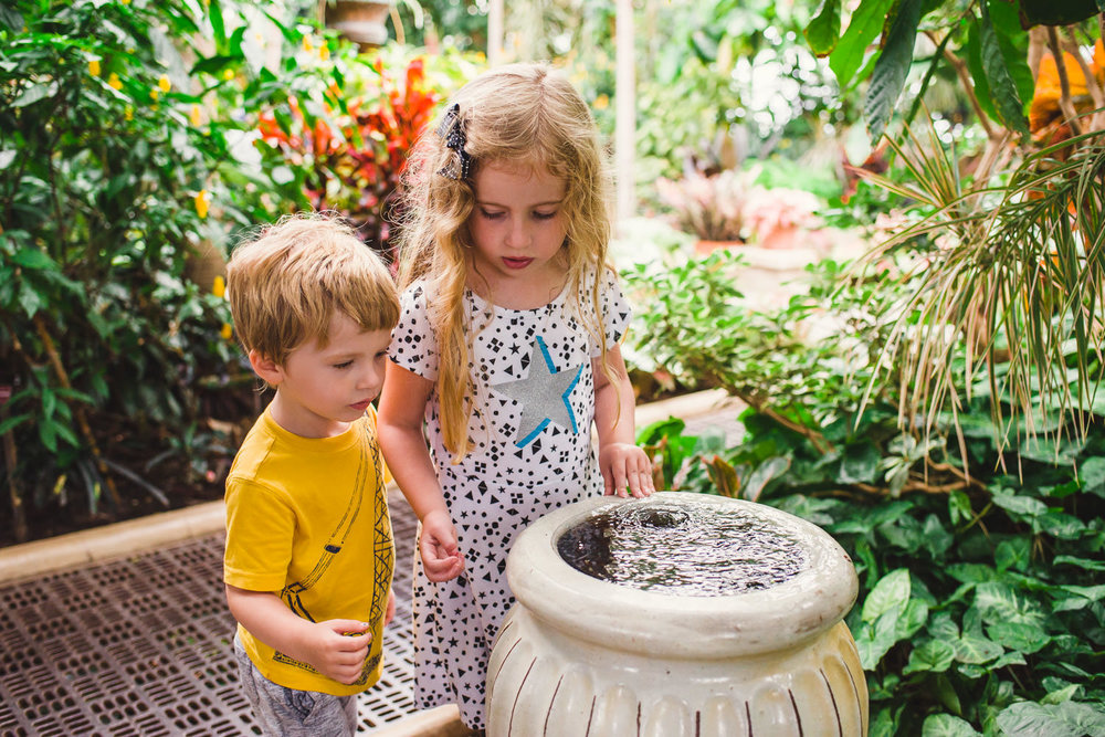 Kids play with a fountain in one of the greenhouses at Planting Fields Arboretum.