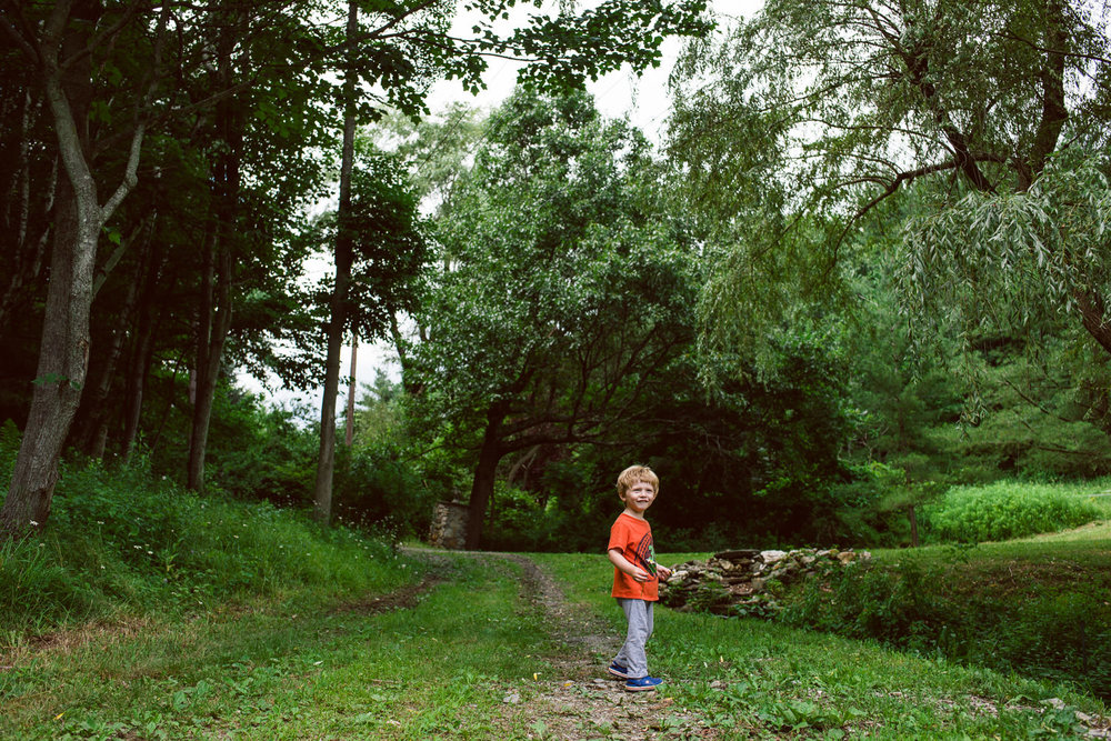 A little boy stands in a wooded area in Copake, NY.