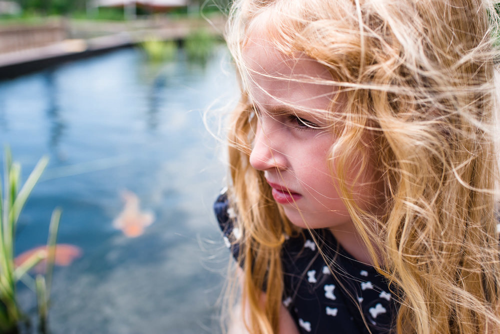 Portrait of a little girl with blonde hair sitting by a koi pond.