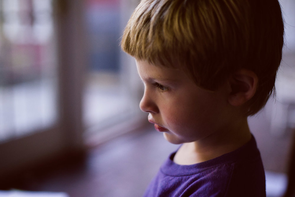 Portrait of a little boy with blonde hair in an enclosed porch.