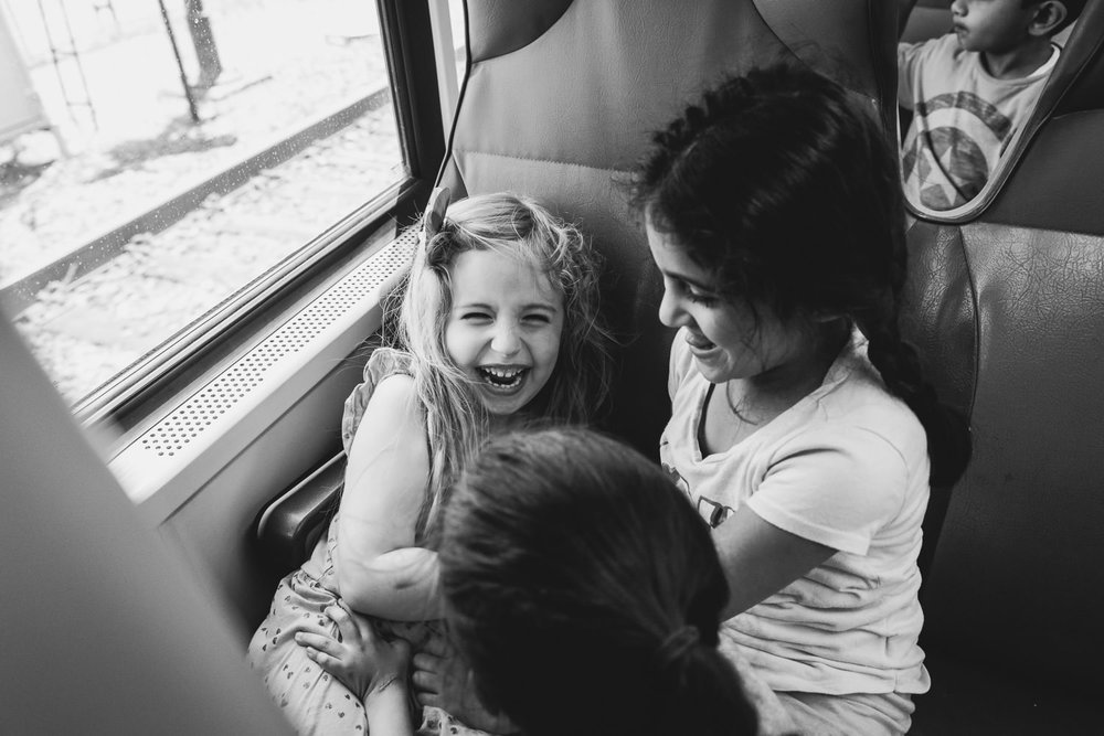 Little girls laugh and tickle each other on the LIRR.