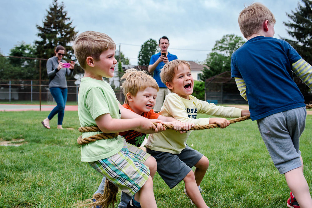 Little boys pull the end of the rope in a tug of war.