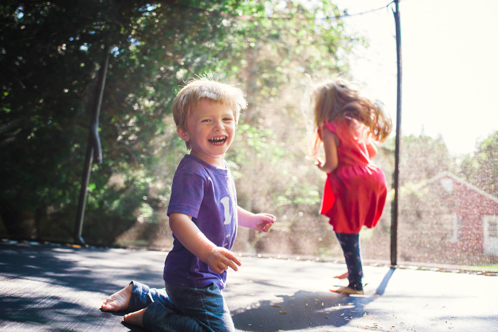A young boy and girl gleefully jump on a trampoline in the summer light.