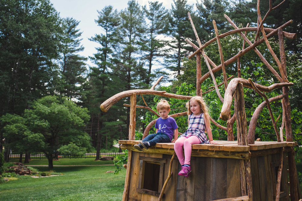 A brother and sister sit atop a playhouse at the Berkshire Botanical Gardens.