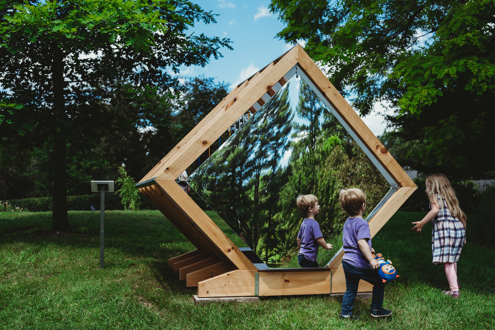 Children run around a mirrored playhouse at the Berkshire Botanical Gardens.