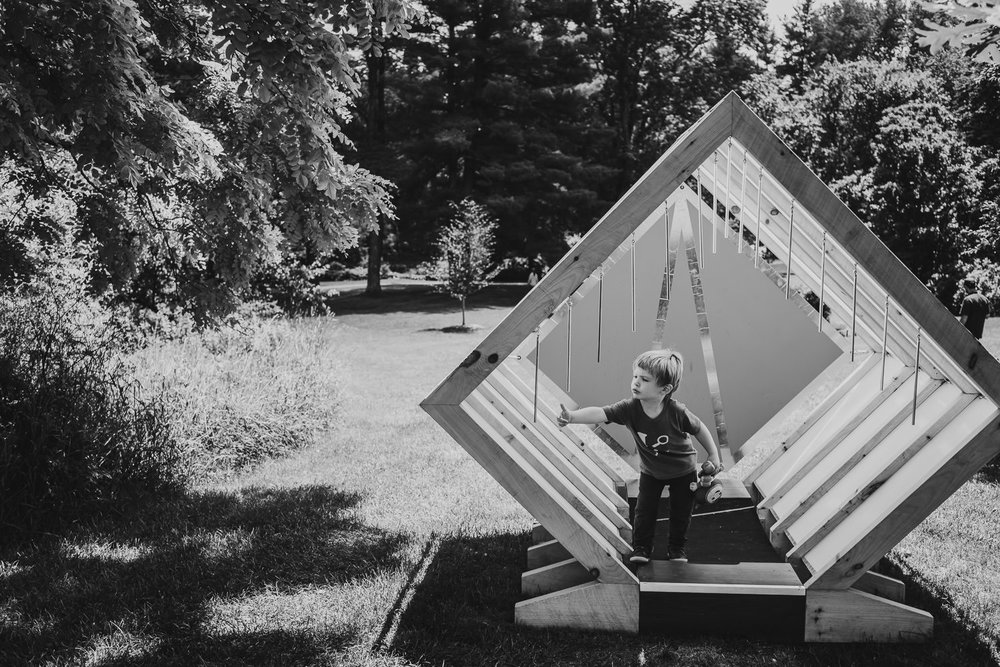 A little boy explores a diamond-shaped playhouse at the Berkshire Botanical Gardens.