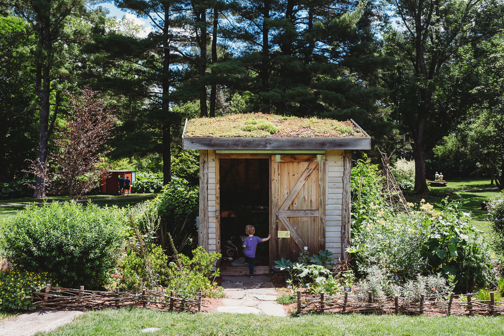A little boy enters a playhouse at the Berkshire Botanical Gardens, designed by Martha Stewart.