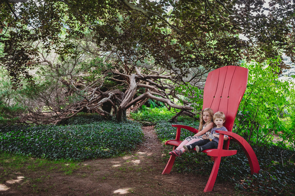 Children sit in a large chair at the Berkshire Botanical Gardens.