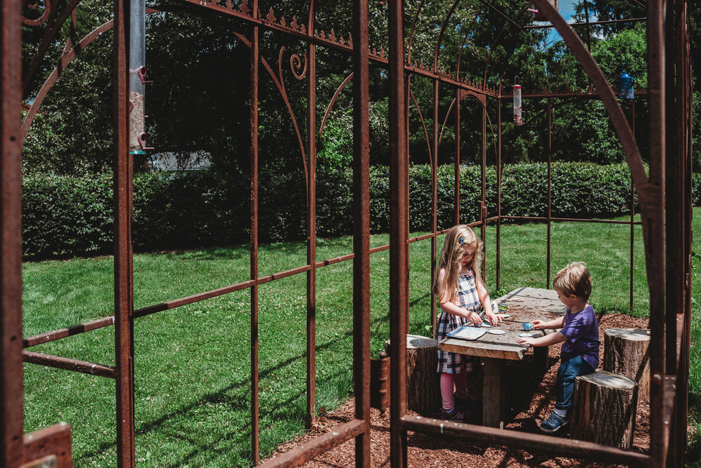 Kids play with a tea set inside a playhouse at the Berkshire Botanical Garden.