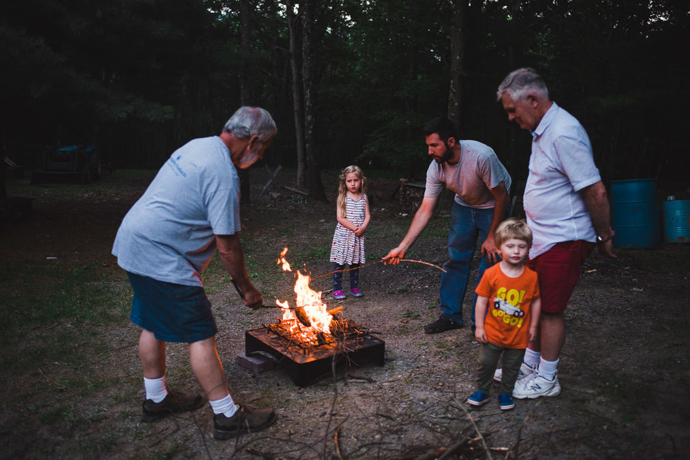 A family makes s'mores over a fire.