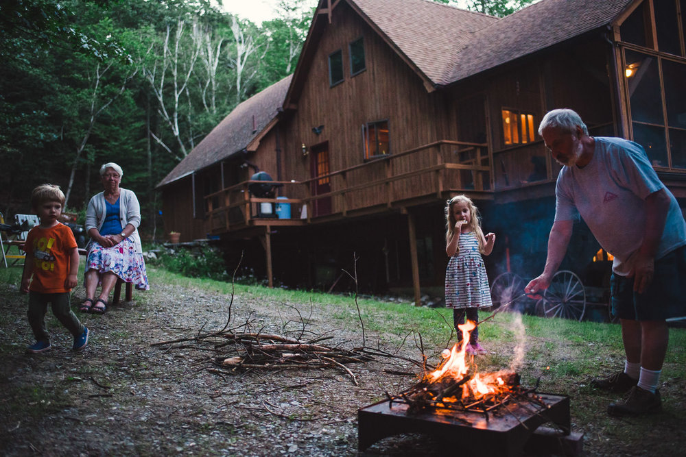 A family makes s'mores over a firepit.