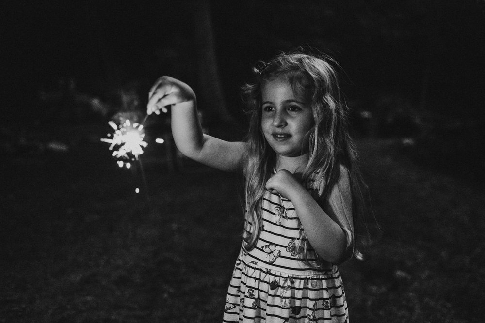 A little girl plays with a sparkler.