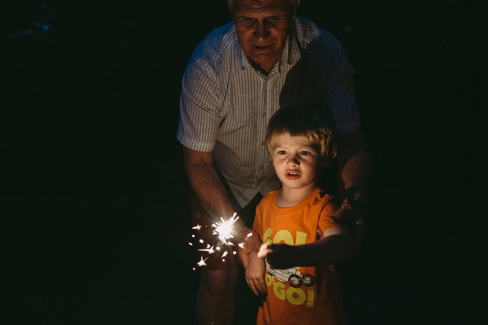 A little boy and his grandfather play with a sparkler.