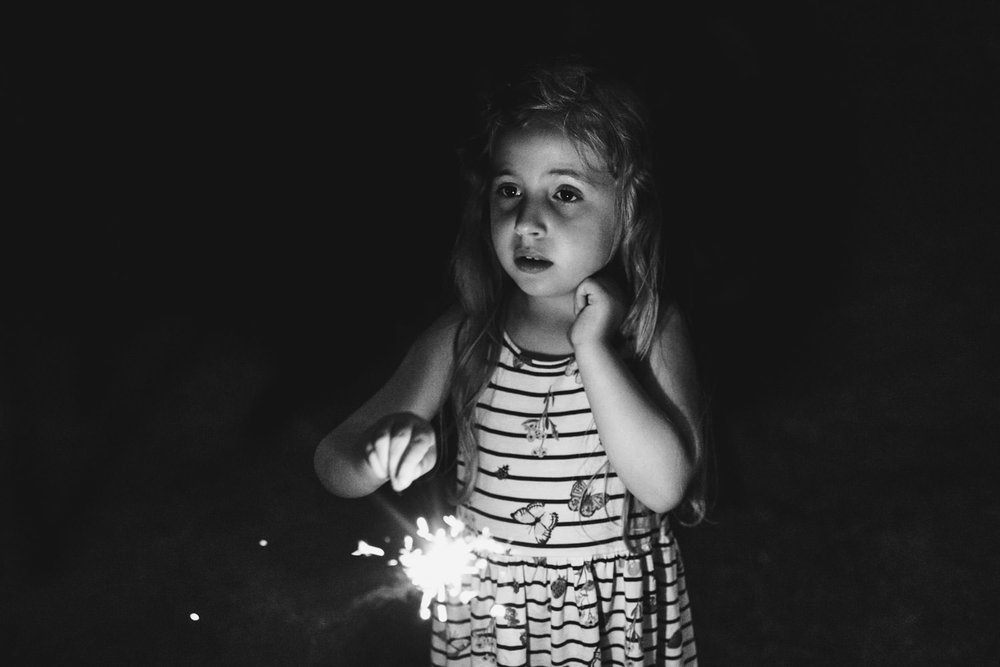 A little girl holds a sparkler.