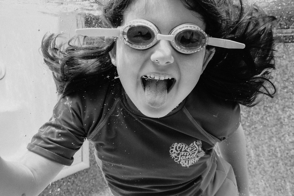 A little girl sticks her tongue out while swimming underwater.