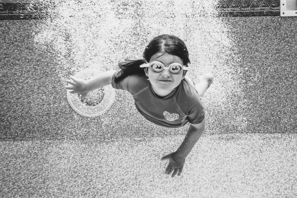 A little girl swims underwater after diving into the pool.