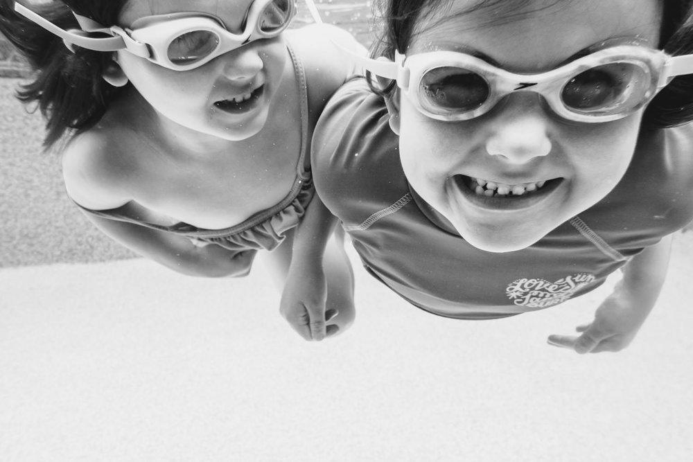 Sisters swim underwater.