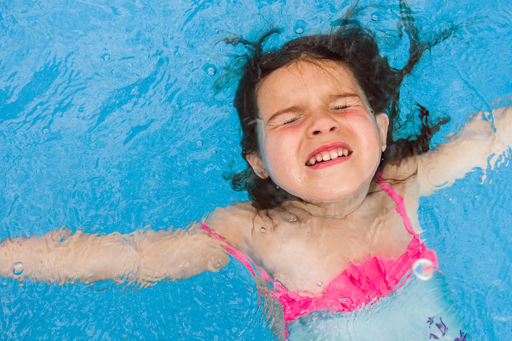 A little girl floats on her back in the pool.